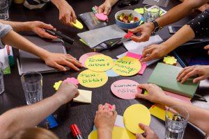 Hände der Workshopteilnehmer auf dem Tisch. Zettel lesen Teamarbeit, Motivation, ...