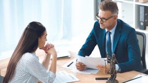 Rechtsanwalt und Klientin sitzen an einem Tisch
