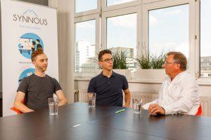 Drei Männer am Tisch in einem Mitarbeitendengespräch