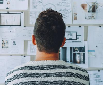 Der Rücken eines Mannes vor einem Whiteborad mit Dokumenten und Zeichnungen